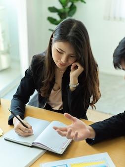 Ritratto della donna di affari che osserva sul taccuino in bianco durante l'incontro con il collega nella sala riunioni