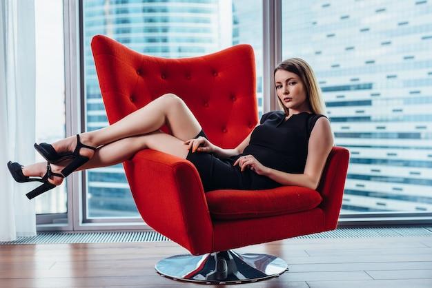 Ritratto di imprenditrice rilassante in elegante poltrona in ufficio.