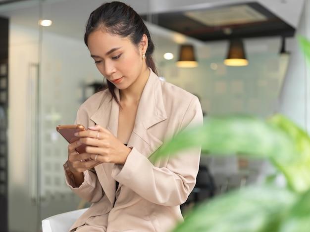 Ritratto della donna di affari che si siede nella stanza dell'ufficio