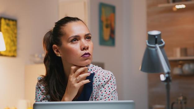 Ritratto di donna d'affari che pensa alla risposta e-mail che lavora a casa seduta sulla scrivania della cucina. primo piano di un dipendente impegnato che utilizza la moderna rete di tecnologia wireless che fa gli straordinari leggendo, scrivendo, cercando