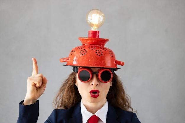 Ritratto di imprenditrice con lampadina contro il muro di cemento grigio. avvio di attività e concetto di idea brillante creativa