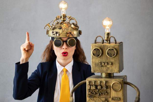 Ritratto di imprenditrice con robot contro il muro di cemento grigio. avvio di attività e concetto di idea brillante creativa