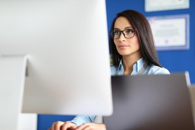 Ritratto della donna di affari che lavora al primo piano del computer