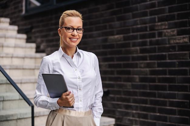 Ritratto di occupato bella sorridente positivo alla moda imprenditrice azienda tablet all'aperto.