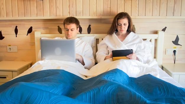 Ritratto di giovane famiglia impegnata che lavora al computer da casa a letto