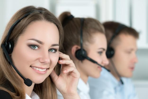 Ritratto del lavoratore del call center accompagnato dal suo team. sorridente operatore del servizio clienti al lavoro. aiuto e concetto di supporto