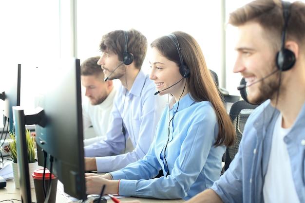 Ritratto di un'operatrice di call center accompagnata dal suo team. operatore di assistenza clienti sorridente al lavoro.