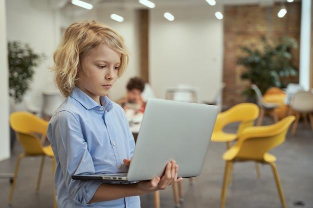 Ritratto di un ragazzino calmo che sembra concentrato mentre tiene e usa il laptop in piedi in un'aula