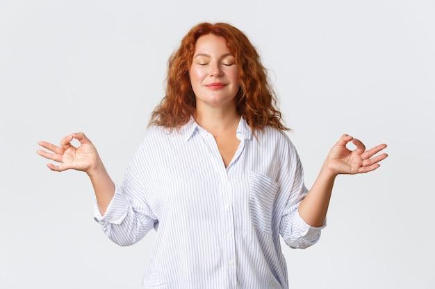 Ritratto di donna di mezza età calma e pacifica, sorridente con i capelli rossi, dall'aspetto paziente e rilassato, chiudi gli occhi e si tiene per mano lateralmente in zen, posa del loto, meditando sul muro bianco.