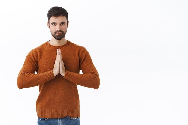 Ritratto di un bell'uomo brunetta calmo e rilassato con barba, stringere le mani in gesto di preghiera o namaste, determinato, essere paziente, meditare, dicendo per favore come chiedere favore