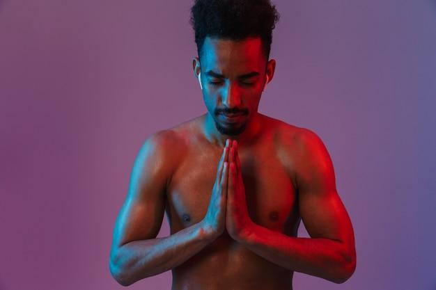 Ritratto di calmante uomo afroamericano senza camicia in posa con auricolari e mani in preghiera isolate su muro viola