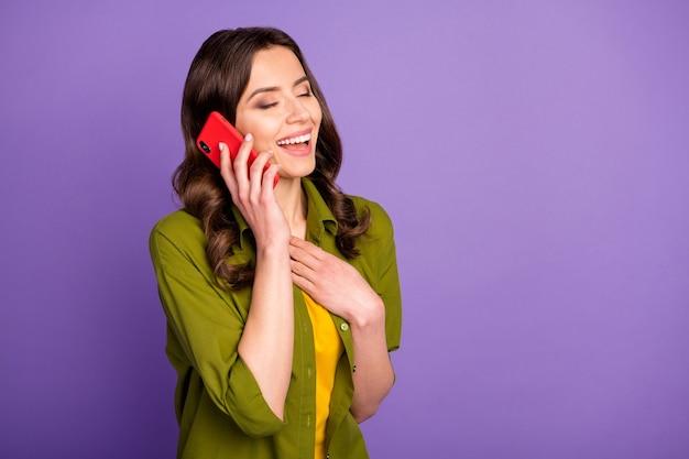 Ritratto di una ragazza dai contenuti candidi che usa lo smartphone chiama la sua amica ascolta uno scherzo divertente che ride tocca il petto della mano indossa uno stile elegante vestito alla moda isolato su uno sfondo di colore viola