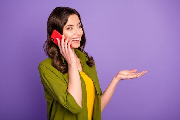 Ritratto di contenuto candido ragazza carina usa smartphone chiama i suoi amici hanno discorsi interessanti indossano abiti di bell'aspetto isolati su uno sfondo di colore vivido viola