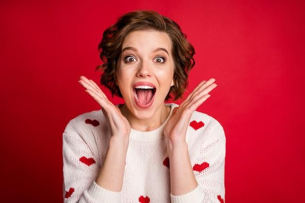 Il ritratto delle mani incrociate dell'amante della ragazza carina adorabile candida indossa il maglione alla moda elegante isolato sulla parete rossa