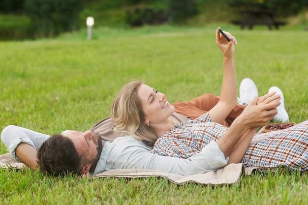 Ritratto di coppia spensierata prendendo selfie sdraiati sull'erba verde nel parco