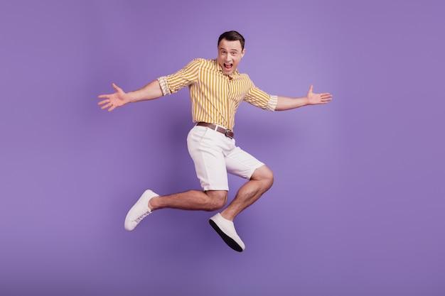 Il ritratto di un pazzo allegro e incurante che salta si diverte a rallegrarsi su sfondo viola
