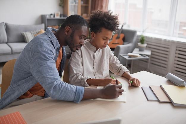Ritratto di padre afroamericano premuroso che aiuta il figlio a fare i compiti o a studiare mentre si siede insieme alla scrivania in un interno minimo di casa