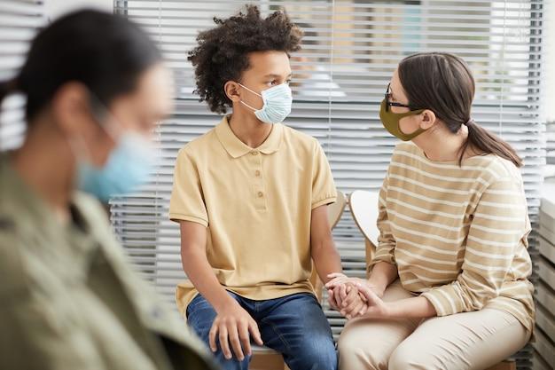 Ritratto di madre premurosa che conforta un adolescente in attesa in fila presso la clinica medica per la vaccinazione, entrambi indossando maschere