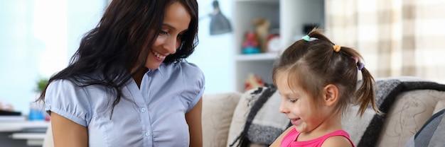 Ritratto della madre premurosa che dà presente alla figlia felice per la festa. mamma allegra che esamina bambina con felicità e orgoglio. maternità e concetto familiare
