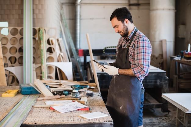 Ritratto di un carpentiere che sta nel suo studio della lavorazione del legno e che tiene compressa digitale