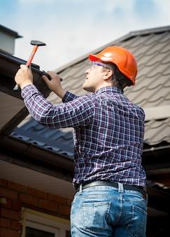 Ritratto di carpentiere al lavoro che ripara il tetto della casa