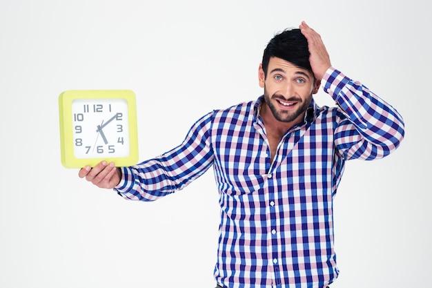 Ritratto di un uomo casual tenendo l'orologio da parete e guardando la parte anteriore isolata su un muro bianco