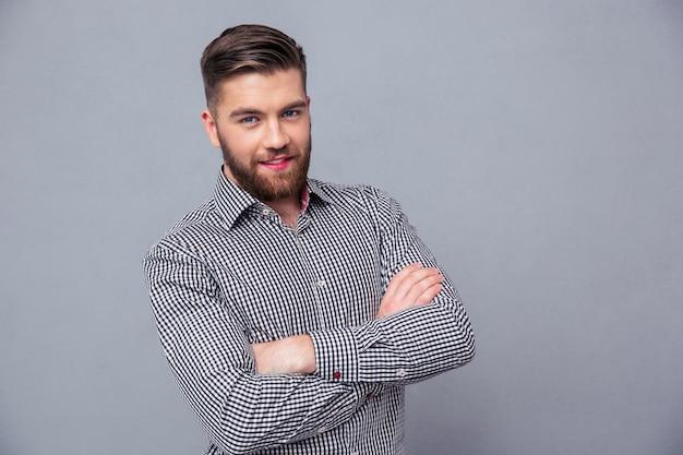 Ritratto di un uomo casual in piedi in camicia con le braccia incrociate sul muro grigio