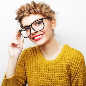 Ritratto di una donna casual con gli occhiali che guarda l'obbiettivo isolato su uno sfondo bianco
