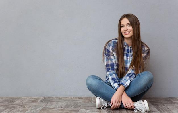 Ritratto di una donna casual seduta sul pavimento e distoglie lo sguardo sul muro grigio