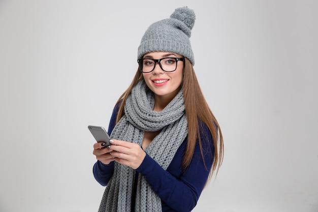 Ritratto di una donna casual in panno invernale utilizzando smartphone e isolato su un muro bianco