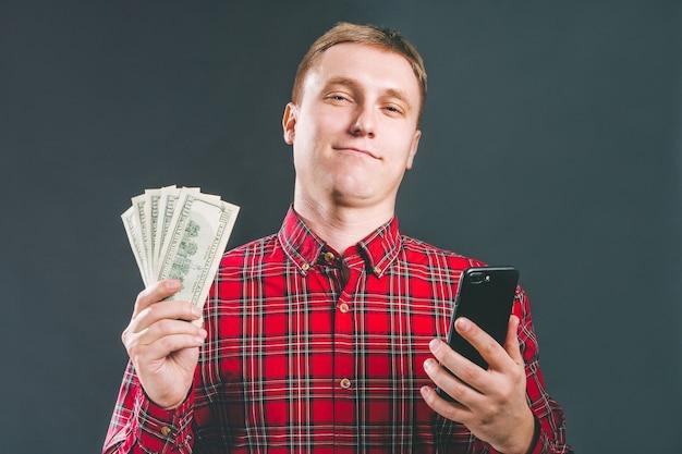 Ritratto di uomo d'affari vestito con indifferenza che tiene reparto di contanti che celebra il suo successo dopo aver effettuato scommesse online nell'applicazione di gioco mobile