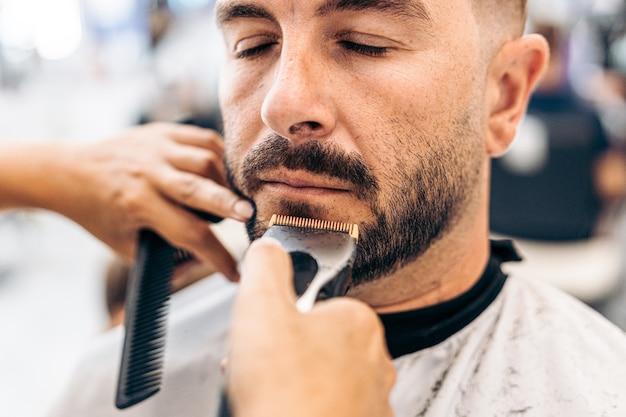 Ritratto di un uomo adulto caucasico con gli occhi chiusi rasato in un negozio di barbiere