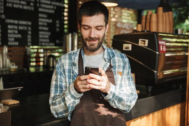 Ritratto di un barista caucasico che indossa un grembiule che sorride e digita sul telefono cellulare in un caffè di strada o in un caffè all'aperto