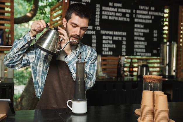 Ritratto di un barista caucasico che indossa un grembiule che fa il caffè mentre si lavora in un caffè di strada o in un caffè all'aperto