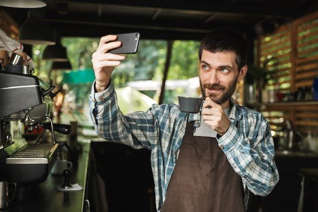 Ritratto di un barista caucasico che indossa un grembiule che scatta foto selfie con una tazza di caffè mentre si lavora in un caffè di strada o in un caffè all'aperto