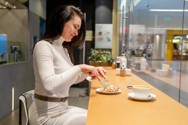 Ritratto di bella donna di mezza età caucasica che mangia un croissant in un caffè. pausa pranzo