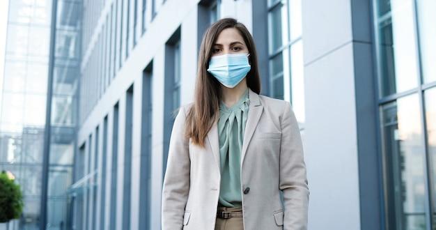 Ritratto di bella donna alla moda caucasica in maschera medica in piedi all'aperto. imprenditrice nella protezione delle vie respiratorie.