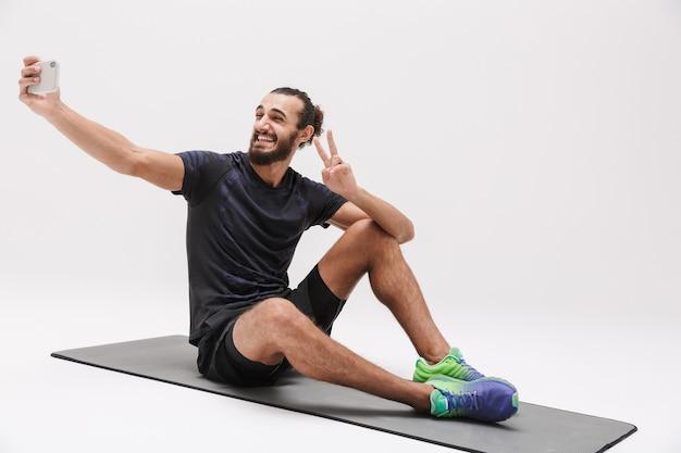Ritratto dello sportivo castana caucasico che prende la foto del selfie sullo smartphone mentre sedendosi sulla stuoia di yoga isolata su white