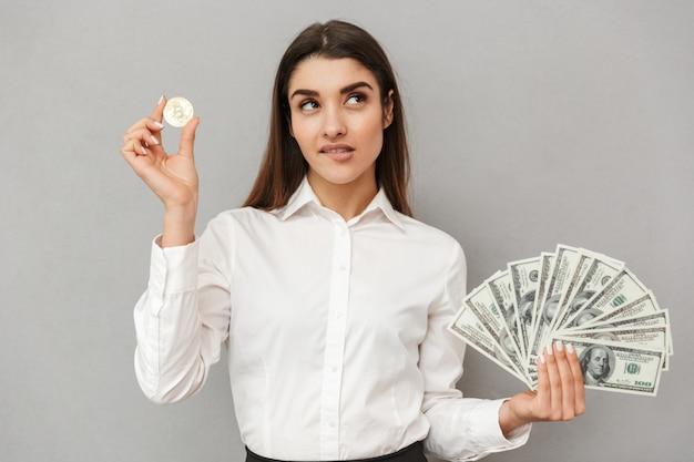Ritratto di donna caucasica bruna con lunghi capelli castani in abbigliamento business che tiene bitcoin e un sacco di banconote da un dollaro di soldi, isolato sopra il muro grigio