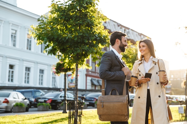 Ritratto di coppia d'affari caucasica uomo e donna in abbigliamento formale che bevono caffè da asporto e parlano insieme mentre si incontrano sulla strada della città
