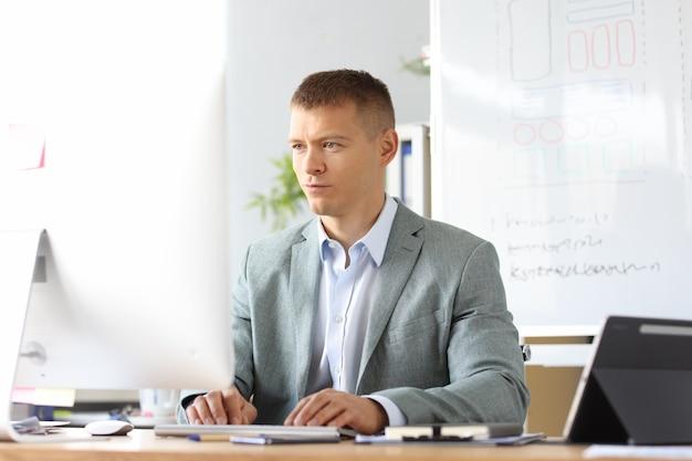 Ritratto di un uomo d'affari caucasico che lavora al computer portatile online in un collega o un lavoratore dell'ufficio domestico