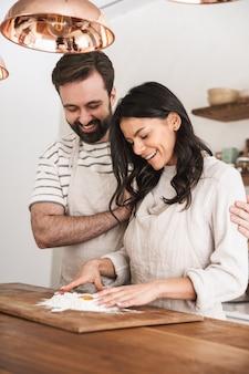 Ritratto di coppia caucasica uomo e donna 30 anni che indossano grembiuli che cucinano pasticceria con farina e uova in cucina a casa