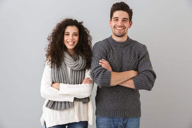 Ritratto di coppia caucasica uomo e donna sorridente e in piedi con le braccia incrociate, isolato sopra il muro grigio