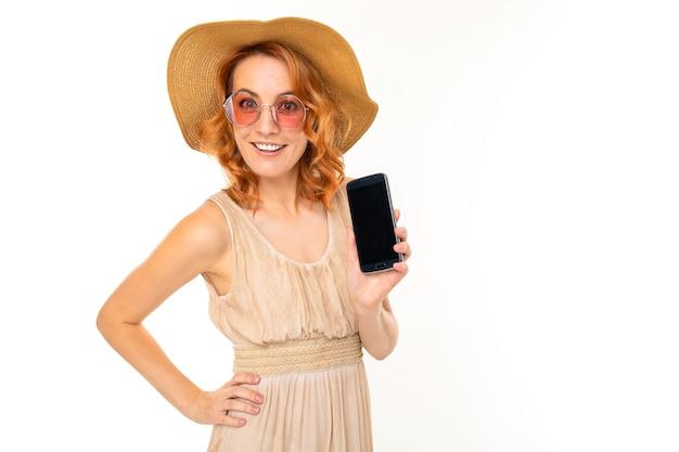 Ritratto di donna caucasica con capelli rossi biondi, bel viso in un bel vestito leggero e sorrisi di grande cappello e servi di internet con il suo telefono