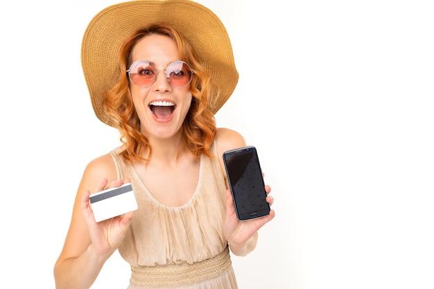Ritratto di donna caucasica con capelli rossi biondi, bel viso in un bel vestito leggero e un grande cappello sorride e mostra il suo telefono con carta di credito