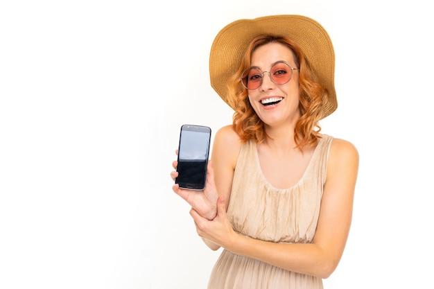 Ritratto di donna caucasica con capelli rossi biondi, bel viso in un bel vestito leggero e un grande cappello sorride e mostra il suo telefono