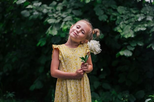 Ritratto di una ragazza caucasica di 6 anni in abito giallo e stivali da pioggia in piedi nel parco con in mano un fiore di peonia