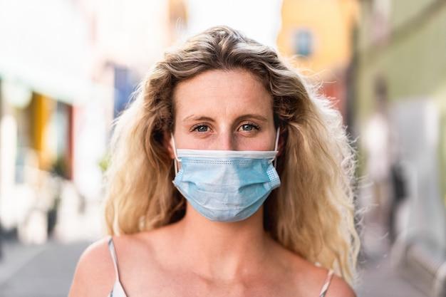Ritratto della ragazza caucasica che indossa maschera protettiva medica per prevenzione della diffusione di coronavirus