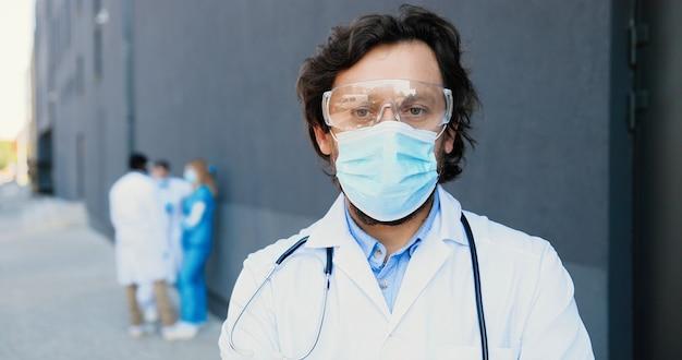 Ritratto del medico caucasico dell'uomo di bell'aspetto in mascherina medica, occhiali di protezione e con lo stetoscopio che guarda l'obbiettivo. primo piano medico maschio in protezione respiratoria. medici multietnici sullo sfondo.