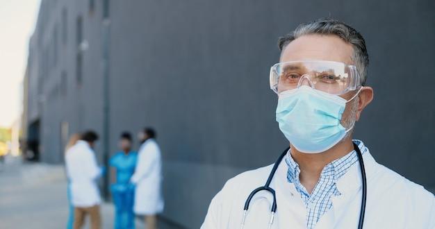 Ritratto del medico caucasico dell'uomo dai capelli grigi in mascherina medica, occhiali protettivi e con lo stetoscopio che guarda l'obbiettivo. primo piano medico maschio in protezione respiratoria. medici multietnici sullo sfondo.